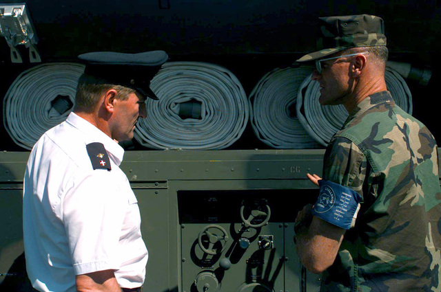 "GUNNERY Sergeant T. E. Hogan gives a brief of his P-19 Aircraft Rescue and Firefighting vehicle to an Estonian firefighter, at a picnic hosted for the citizens of Paldiski, Estonia during BALTIC CHALLENGE '97. Over 4000 local citizens attended the event hosted by the American Embassy and the Coca-Cola company. The picnic was setup and prepared by US Marines. BALTIC CHALLENGE is a multinational exercise conducted in the spirit of NATO's Partnership for Peace (PfP) initiative. More than 2600 military personnel from Denmark, Estonia, Finland, Latvia, Lithuania, Norway, Sweden, and the US, will participate in the second ""in the spirit of PfP"" land exercises conducted in the Baltic region...."