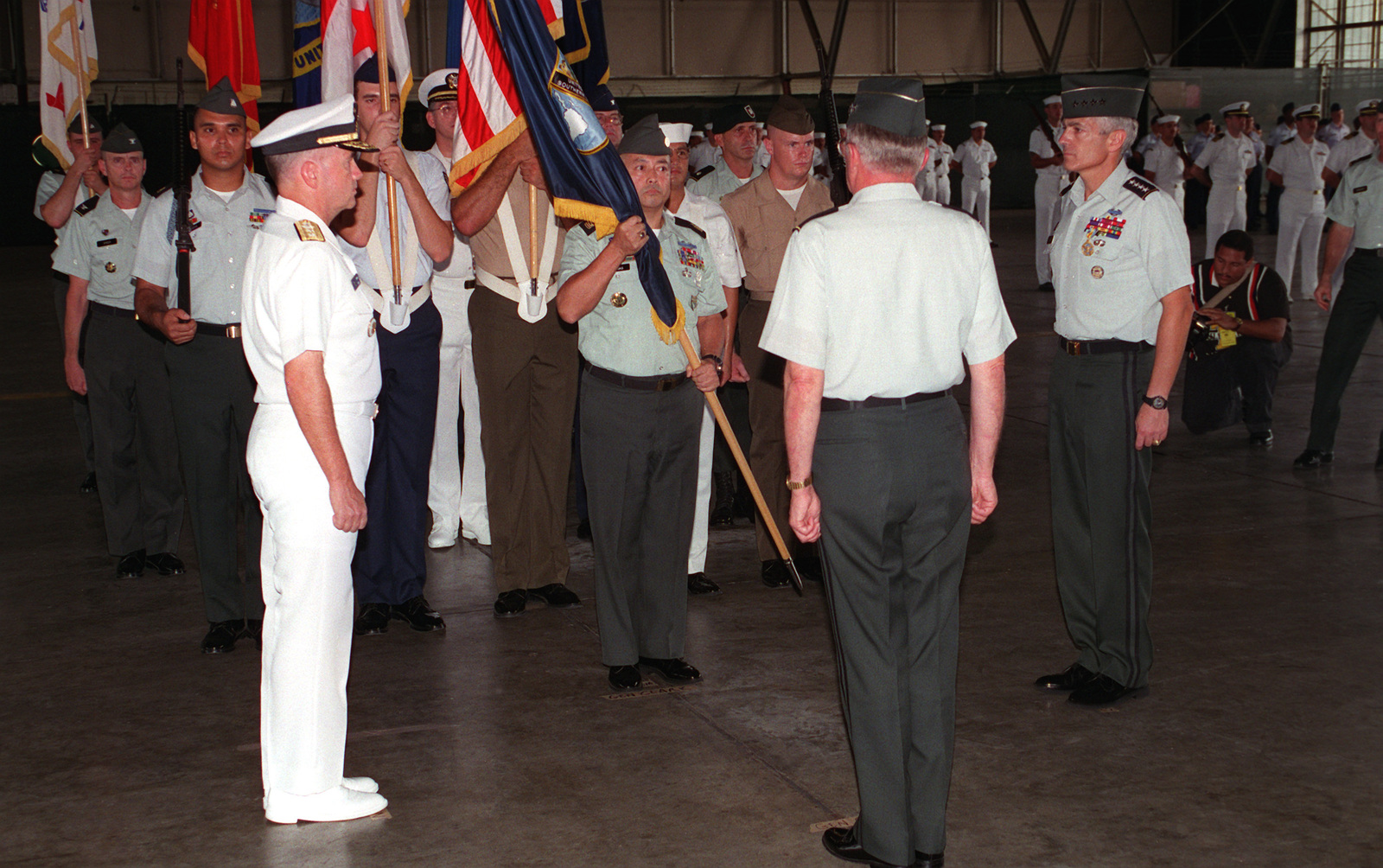 RADM Walter Doran, (left) Acting Commander in CHIEF (CINC) U.S. Southern Command (USSOUTHCOM), waits as USSOUTHCOM's CSM Carlos Legoas prepares for the ceremonial passing of the command flag with GEN John Shalikashvili (back to camera), Chairman of the Joint Chiefs of STAFF, and outgoing CINC, GEN Wesley Clark during the Change of Command ceremonies