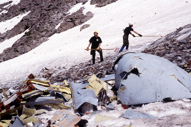 A1C Myca Romes (left) and SPT Luke Closson (right) collect A-10 debris on the snow covered slope with rakes. This rubble was deemed not critical to the accident investigation and will be airlifted off the mountainside to be properly disposed of