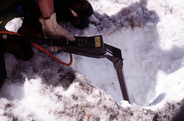 Explosive Ordnance Disposal (EOD) member conducts a subsurface search with a MK-26 Ferrous Ordnance Locator on the snow covered upper debris field of the A-10 crash site. The MK-26 enables EOD members to locate metal objects up to 14 feet under the snow