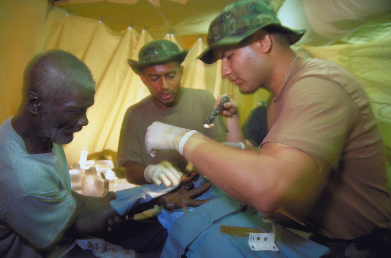 Dr. (CAPT.) Sebastian F. Cherian and AIRMAN 1ST Class Robert D. Gomez with the 49th Medical Group, Holloman Air Force Base, N.M. works on the Guyanese man's badly cut finger. The 49th Medical Group deployed 35 personnel in support of New Horizon '97, the first combined humanitarian and civic assistance exercise conducted between the United States and Guyana. Military personnel from Air Force, Air Force Reserve & National Guard, Army, Army National Guard and Marine Corps participated in the exercise which included engineering and medical readiness training