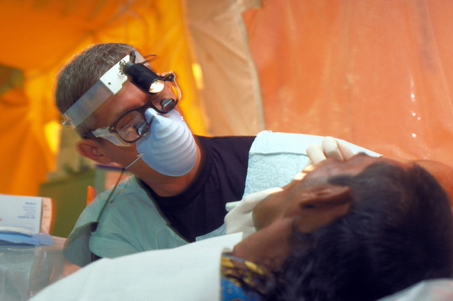 Dr. Victor P. Bradford, a dentist with the 49th Medical Group, Holloman Air Force Base, N.M. places gauze in the mouth of a Guyanese patient. The 49th Medical Group deployed 35 personnel in support of New Horizon '97, first combined humanitarian and civic assistance exercise conducted between the United States and Guyana. Military personnel from the Air Force, Air Force Reserve & National Guard, Army, Army National Guard and Marine Corps participated in the exercise which included engineering and medical readiness training