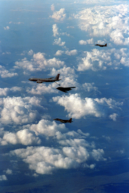 Vertical aerial view of a KC-135R tanker with the 911th ARS (Red Eagles) from Grand Forks, North Dakota, as it refuels a B-2 bomber that is on its way to an airshow at RAF Fairford, England. The tanker crew is attached to the European tanker task force at RAF Mildenhall. The two F-15C Eagle escorts are with the 493rd Fighter Squadron, 48th FW at RAF Lakenheath