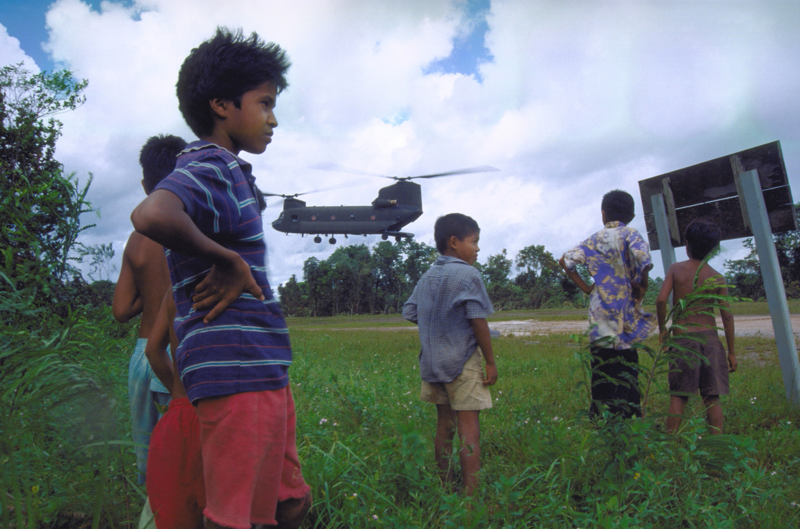 Children from the village of Kumaka wait at Bemechi Air Strip as a CH-47 helicopter prepares to land in the background. The helicopter from Detachment 1, Company F, 106th Aviation are supporting the first combined humanitarian and civic assistance exercise conducted between the United States and Guyana. Military personnel from Air Force, Air Force Reserve & National Guard, Army, Army National Guard and Marine Corps participated in the exercise which included engineering and medical readiness training