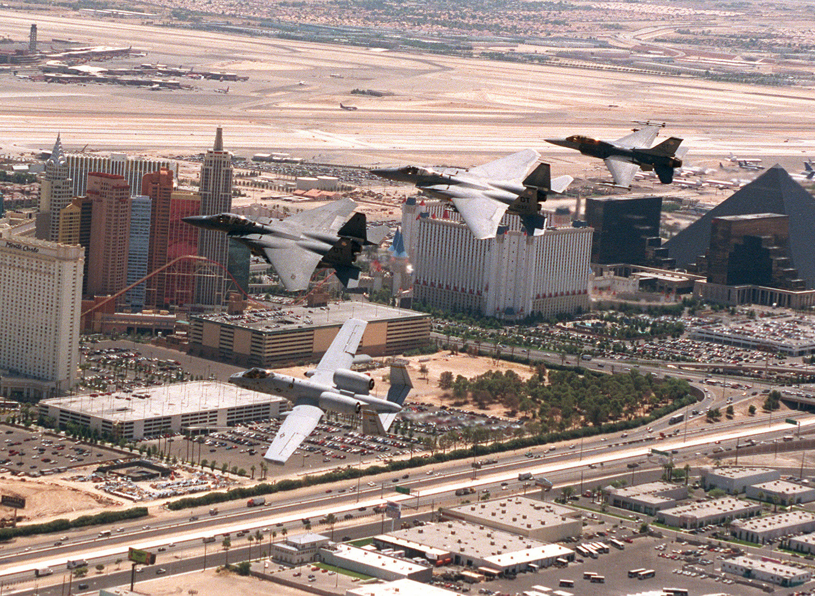 """An A-10, F-15E, F-15C and a F-16D from Nellis AFB, fly a finger tip formation over the Las Vegas """"Strip"""" with the (Left to Right) Monte Carlo, New York - New York, Excalibur and the Luxor hotels in the background"""