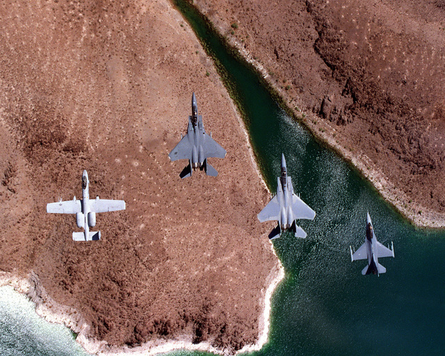 An A-10, F-15E, F-15C and F-16D all from Nellis AFB, Nev., fly over Lake Mead in a finger tip formation just before crossing land