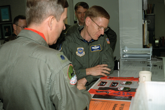 """LGEN John Handy (center), 21st Air Force commander, admires a 41st Airlift Squadron """"Black Cat"""" flying scarf, patches, and name tags presented to him by LTC Ken Menzie (left), 41st Airlift Squadron commander at COL David L. Johnson (background), 43rd Airlift Wing commander, looks on"""