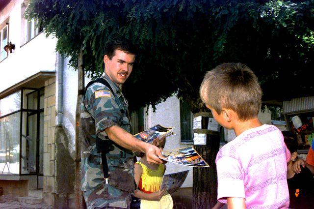 US Army Reserve, Sergeant (SGT) Thomas of the 304th Psychological Operation (PSYOPS) Unit hands a Stabilization Force (SFOR) publication to a boy in the town of Rudo, inside the Republic of Serbska, Bosnia-Herzegovina. Thompson's job is to gain rapport with the locals and assist them with basic needs like school books, supplies and often the connection of a phone line in rural villages. In addition, the unit passes out a monthly world event magazine, a DC Superman comic book outlining mine awareness and several informative voting guides for the September municipal elections. Three teams of the 304th Psychological Operation unit are based out of Sarajevo, BIH. Operation JOINT GUARD 31 July...
