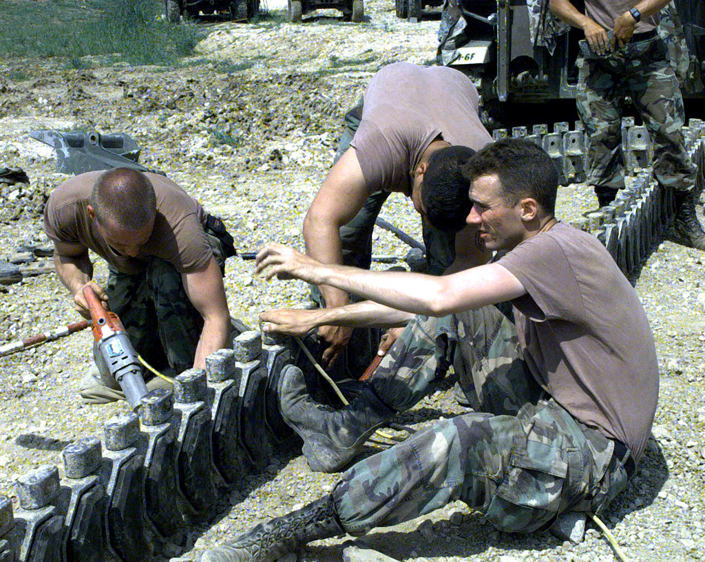 US Army soldiers of Alpha Battery, 1ST Battalion, 6th Field Artillery, 1ST Infantry Division (Mechanized), Bamberg, Germany, attached to Camp McGovern, Bosnia and Herzegovnia, replace worn out track pads with new ones on a M109 howitzer. Operation JOINT GUARD, 31 July 1997