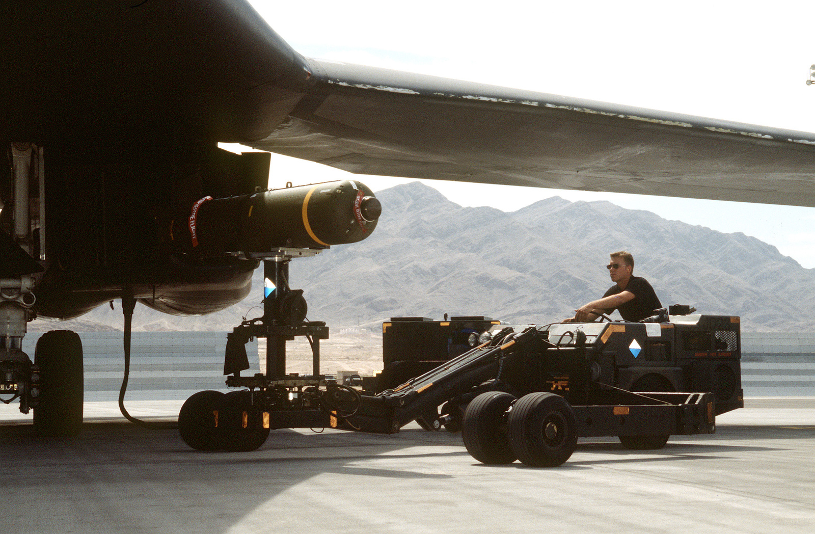 A1C Corey Futch from the 28th Bomb Squadron, 7th Bomb Wing, Dyess Air Force Base, Texas, loads a BDU bomb into a B-1B bomber using an MJ-1 weapons loader during a RED FLAG exercise. Exact Date Shot Unknown