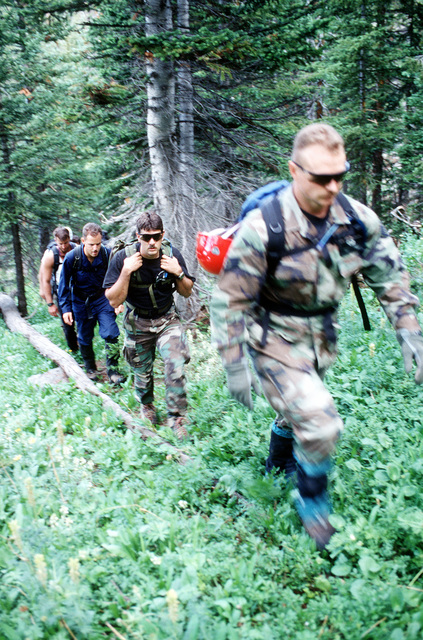 A-10 recovery team members hike through the basin in search of any remnants of the four 500 pound Mark 82 bombs that were carried by the A-10 that crashed on Gold Dust Peak