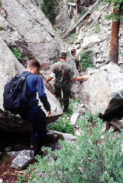 Members of the A-10 recovery team descend one of the many unstable rock piles as they search along the East Brush Creek for remnants of the A-10 or the four 500 pound Mark 82 bombs. An Army UH-1N helicopter can be seen flying near one of the peaks