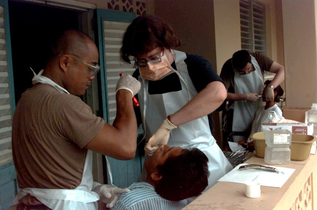 SSGT David Castillo, a radiology technician with 126th Medical Squadron, Illinois Air National Guard, O'Hare International Airport, Chicago, IL, assists dentist MAJ Susan Cleereman, from the 110th Medical Squadron, Michigan Air National Guard, Battle Creek, MI, performs a tooth extraction on a Guyanese farmer during a Medical Civil Assistance Program (MEDCAP) held in support of the first combined humanitarian and civic assistance exercise conducted between the United States and Guyana. Military personnel from the Air Force, Air Force Reserve and National Guard, Army, Army National Guard and Marine Corps participated in the exercise which included engineering and medical readiness training