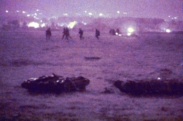 "(Night Scope PHOTO.) US Army soldiers of A Company, 1ST Battalion, 13th Armor, 3rd Brigade, 1ST Armored Division (Team Tank) , as they move to their positions after arriving at the former living area Steele Castle, designated Landing Zone Castle, during an air assault training mission. In the foreground are mock ""munitions"" waiting to be slingloaded. Bosnia-Herzegovina, Operation JOINT GUARD, 13 August 1997"
