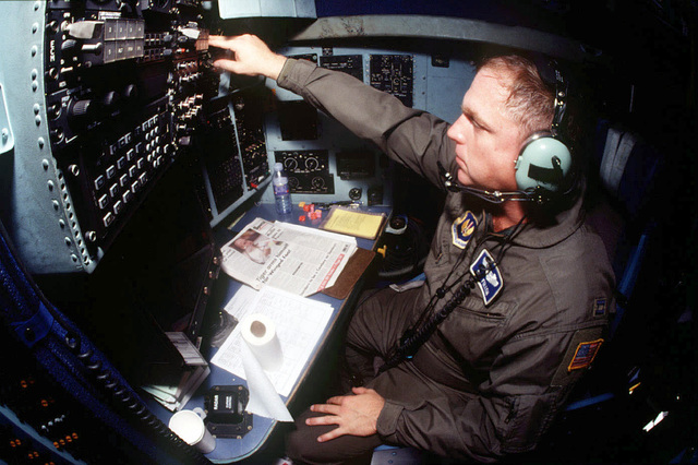 USAF Captain Skip Fullem, C-130 Hercules navigator of the 37th Airlift Squadron, reaches to flip a switch while going through his pre-flight checklist at his station in the Hercules' cockpit