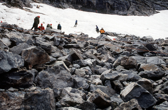 A-10 recovery team members search for remnants of the aircraft on the snow covered slopes as well as the shifting rock piles caused by recent rains