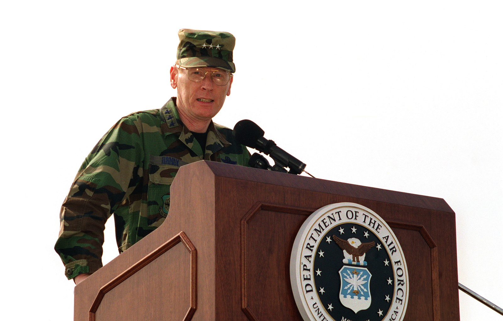 LGEN John W. Handy, Commander 21st Air Force, McGuire Air Force Base, New Jersey, speaks from a podium during the ceremonies marking the arrival of the new 60K Tunner Loader. The new loader will support a 60,000 pound maximum load, carry 463L pallets, is 65 feet long, 14 feet wide and has a maximum height of 18 feet
