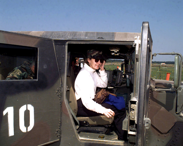 Texas Republican Senator, Kay Bailey Hutchison takes her seat in the front of an M998 High-Mobility Multipurpose Wheeled Vehicle (HMMWV), Pratially visible through rear door window is United States Army, General Wesley K. Clark, Supreme Allied Commander, Europe and Commander-in-CHIEF, United States European Command. The vehicle will take them to the community center area in Stari Rasadnik, Bosnia-Herzegovina. Operation JOINT GUARD, 15 August 1997