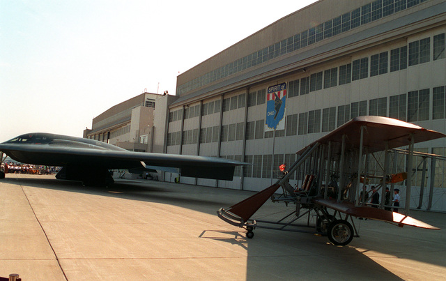 """The B-2 """"Spirit of Ohio"""" stealth bomber sits next to the Wright Flyer in front of the hangar during dedication ceremonies for the new B-2 bomber"""