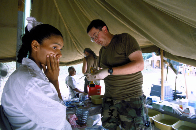 A young girl and local resident of Malali, looks apprehensive as Dr. (MAJ.) Pete Krafcisin, a dentist assigned to the 126th Medical Squadron, O'Hare Field, Chicago, Ill., prepares to extract one of her teeth. The 126th personnel provided three days of medical care to the local population in support of the first combined humanitarian and civic assistance exercise conducted between the United States and Guyana. Military personnel from Air Force, Air Force Reserve & National Guard, Army, Army National Guard and Marine Corps participated in the exercise which included engineering and medical readiness training