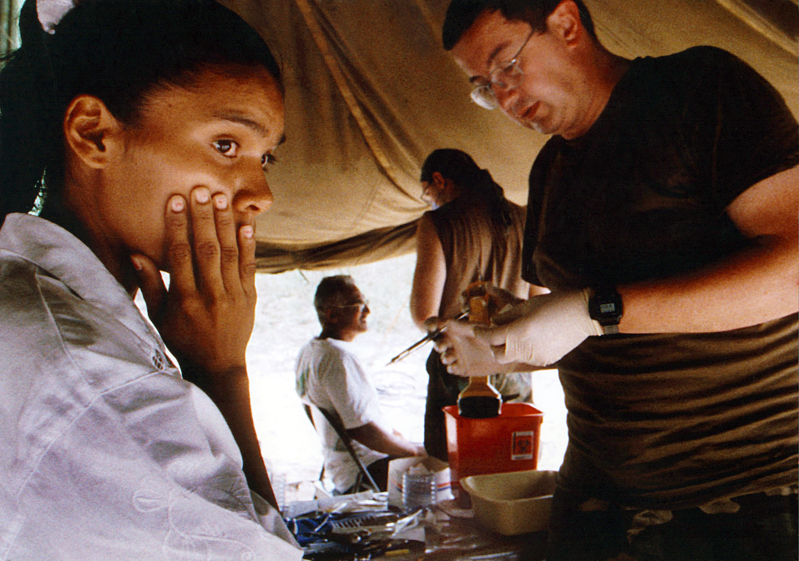 Military Photographer of the Year Winner 1997 Title: Painful Anticipation Category: News; Portfolio Place: 3rd Place News; 3rd Place Portfolio Caption: A young girl, and local resident of Malali, Guyana, is about to get her tooth extracted by Major Pete Krafcisin, a dentist assigned to the 126th Medical Squadron, O'hare Field, Chicago, Illinois, at the site of a New Horizons medical aid tent on August 19, 1997. Medical technicians are providing aid to the local population in support of New Horizon 97, a humanitarian and medical readiness exercise