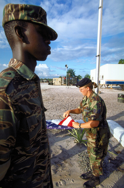 A Guyana Defense Force specialist stands by as STAFF SGT. Denise Watson, 140th Security Forces Squadron, Air National Guard, Buckley Field, Colo. folds the American flag during retreat ceremonies at Camp Stephenson during New Horizon '97, first combined humanitarian and civic assistance exercise conducted between the United States and Guyana. Military personnel from the Air Force, Air Force Reserve & National Guard, Army, Army National Guard and Marine Corps participated in the exercise which included engineering and medical readiness training