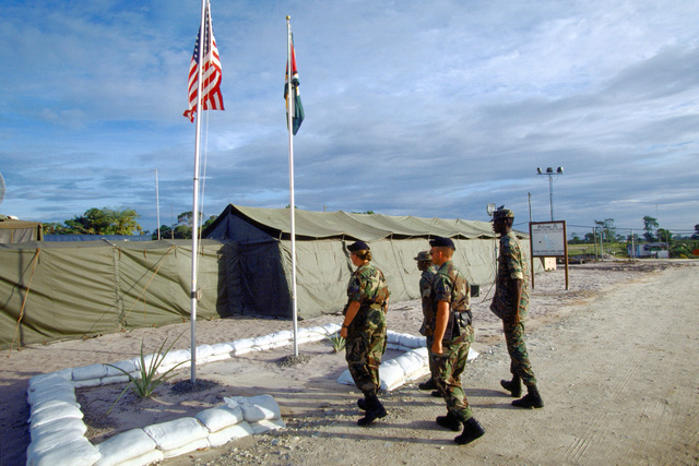 AIRMAN 1ST Class Chris Stein and STAFF SGT. Denise Watson, Air National Guard Security Forces, 140th Security Forces Squadron, Buckley Field, Colo. along with security specialists from the Guyana Defense Force approach the flag poles as part of the Camp Stephenson retreat ceremonies. The 140th provided security for the camp, that was the home for Combined Task Force Falcon members participating in support of the first combined humanitarian and civic assistance exercise conducted between the United States and Guyana. Military personnel from Air Force, Air Force Reserve & National Guard, Army, Army National Guard and Marine Corps participated in the exercise which included engineering and ...