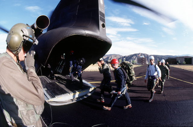 Army SGT Bosmans, a CH-47 flight engineer assigned to Detachment 1, Company G, 140th Aviation, Nevada Army National Guard, watches as A-10 recovery team members aboard the helicopter to begin another day of searching for remnants of the aircraft that crashed near Gold Dust Peak