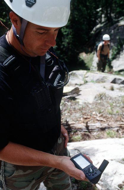 MSGT Eric Wass (left), an Explosive Ordnance Disposal member, gets a location fix with his portable global positioning system as SRA Scott McCullough (background) surveys the area in an attempt to locate any remnants of the A-10 and the four 500 pound Mark 82 bombs