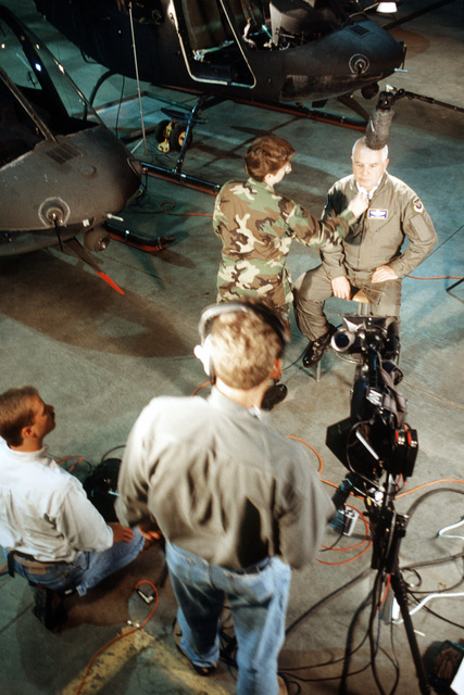 BGEN Don Streater, commander of the A-10 recovery operation, sits as sound and camera technicians from ABC's Good Morning America program prepare for a live interview in the hangar of the Colorado Army National Guard's High Altitude Training Site