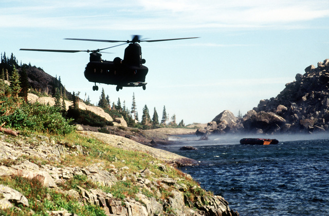 A CH-47 from Detachment 1, Company G, 140th Aviation, Nevada Army National Guard, drops off the Navy's Zodiac boat. The Navy's Explosive Ordnance Disposal Mobile Unit 7 from San Diego, California will search the lake, one of six near the crash site, for remnants of the four 500 pound bombs carried by the A-10 that crashed on Gold Dust Peak
