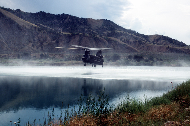 A CH-47 from Detachment 1, Company G, 140th Aviation, Nevada Army National Guard, starts its approach over New York Lake to drop off the Navy's Zodiac boat. The Navy's Explosive Ordnance Disposal Mobile Unit 7 from San Diego, California will search the lake, one of six near the crash site, for remnants of the four 500 pound bombs carried by the A-10 that crashed on Gold Dust Peak