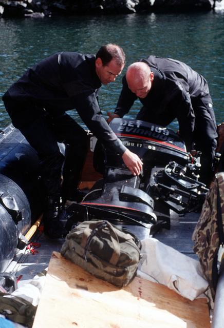 Aviation Ordnanceman CHIEF George Wilson (left) and Storekeeper First Class Alan Beaty (right) load their outboard motor into the Zodiac boat on New York Lake where the Navy's Explosive Ordnance Disposal Mobile Unit 7 from San Diego, California will search for remnants of the four 500 pound bombs carried by the A-10 that crashed near Gold Dust Peak