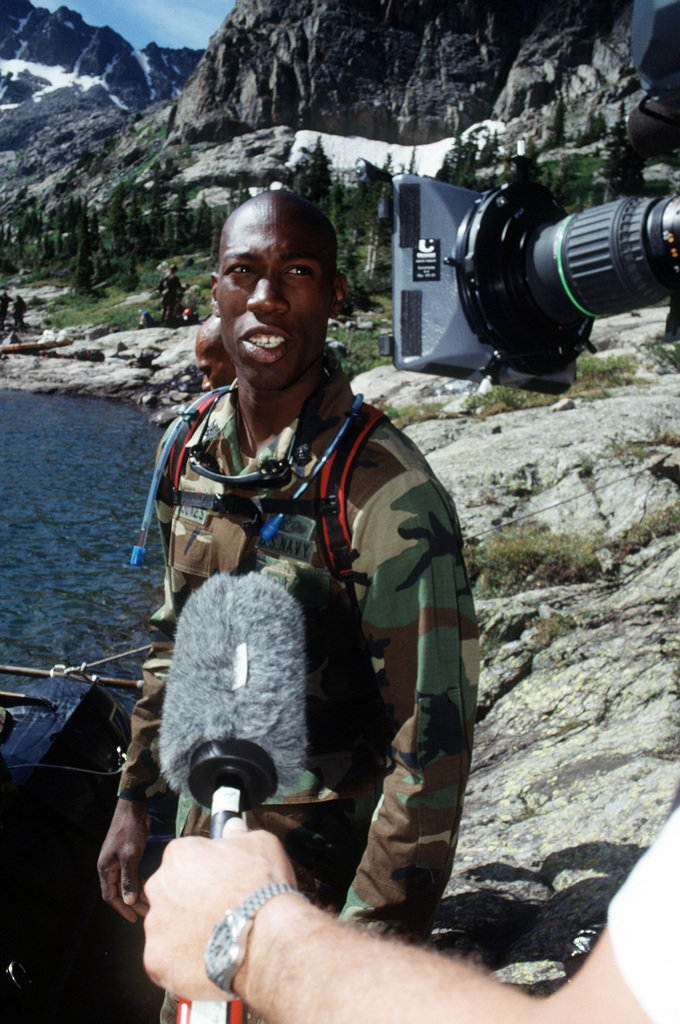 Electrical Technician Talmadge Jones, Jr. fields questions from ABC and NBC camera crews as Naval Explosive Ordnance Disposal Mobile Unit 7 technicians from San Diego, California prepare for their initial search operation for the four missing 500 pound Mark 82 bombs carried by the A-10 that crashed near Gold Dust Peak