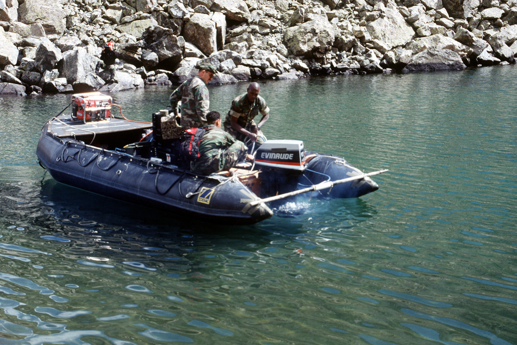 Members of the Naval Explosive Ordnance Disposal Mobile Unit 7 members from San Diego, California set out on the Zodiac boat to begin their initial search for the four missing 500 pound Mark 82 bombs carried by the A-10 that crashed near Gold Dust Peak. New York Lake is the first of six lakes in the Gold Dust Peak that will be searched