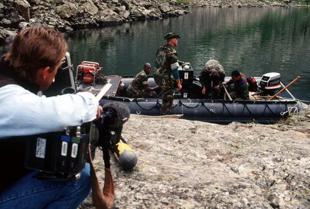 Naval Explosive Ordnance Disposal technicians from Explosive Ordnance Disposal Mobile Unit 7 from San Diego, California prepare their Zodiac boat as they begin their search operations for the four missing 500 pound Mark 82 bombs carried by the A-10 that crashed near Gold Dust Peak. As the crew prepares to launch their boat, an NBC cameraman (left) captures the activity