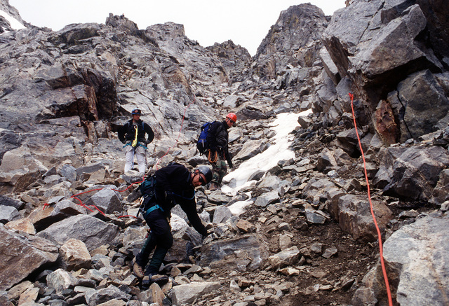 The A-10 recovery team members traverese the rocky and hazardous terrain near the top of Gold Dust Peak