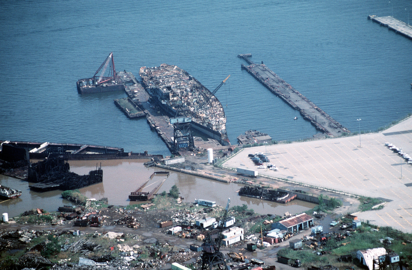 Aerial starboard bow view of the aircraft carrier CORAL SEA (CV 43) in the late stages of being scrapped out at the Fairfield Terminal of the new Patapsco Marine Salvage Company. The PMS Co. took over operations from the bankrupt Seawitch Salvage Company
