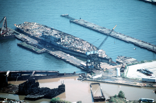 Aerial starboard bow view of the aircraft carrier CORAL SEA (CV 43) moored at the Lambert Point facility of the new Patapsco Marine Salvage Company. The ship is in the late stages of being scrapped out