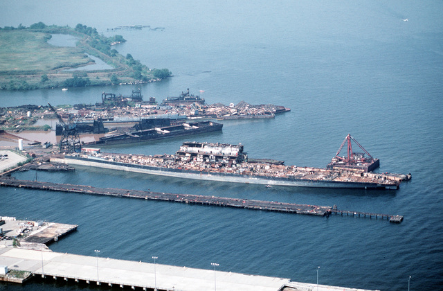 Aerial starboard side view of the aircraft carrier CORAL SEA (CV 43) in the late stages of being scrapped out at the Lambert Point facility of the new Patapsco Marine Salvage Company