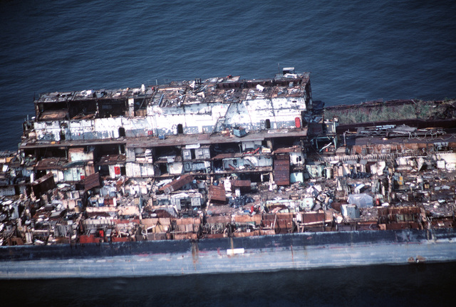 Aerial view from the port side of a section of the aircraft carrier CORAL SEA (CV 43) from amidships to aft of the old island location. CV 43 is in the late stages of being scrapped out at the Lambert Point facility of the new Patapsco Marine Salvage Company