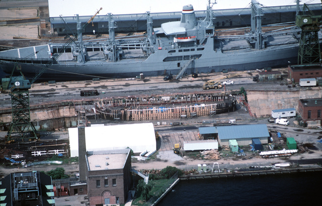 Aerial view of the historic 36 gun sailing frigate USS CONSTELLATION (Former IX-20) in a small drydock to the north of Fort McHenry. The ship began a lengthy rebuild last March to correct serious deterioration of the hull structure. In this view extra planking holds the sides in place. Also note that the main gun deck has been removed. The ship is being returned to her Civil War appearance. The RRF cargo ship CAPE ARCHWAY (T-AK-5011) is tied up in the background at the Maryland Port Administration pier No. 3