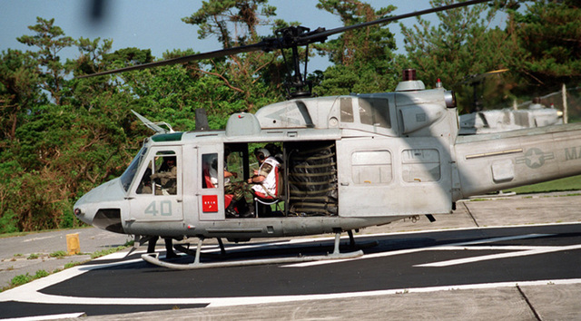A UH-1 helicopter prepares to lift-off on a flight to Camp Kinser. General Charles C. Krulak, Commandant of the Marine Corps, straps himself in for an enjoyable flight
