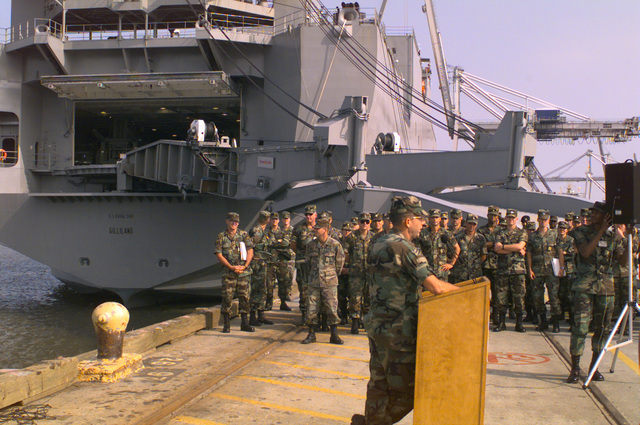MAJ. GEN. James C. Riley, commander, 3d Infantry Division (Mechanized), briefs soldiers at the Port of Savannah at the conclusion of Deployment Exercise 97-02. A stern view of the US Naval Ship (USNS) GILLILAND (T-AKR-298), which was used during loading/unloading procedures, is tied to the pier