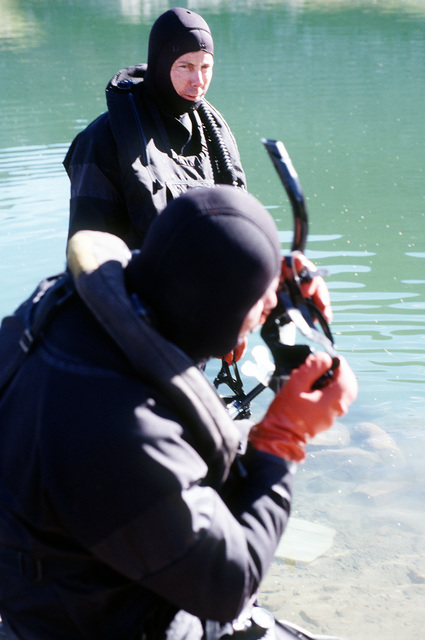 Naval Explosive Ordnance Disposal Mobile Unit 7 technicians Signalman First Class Joel Blea (foreground) and Quartermaster Second Class Gary Hakes prepare to swim in one of the ponds west of New York Lake in search of remnants of four 500 pound Mark 82 bombs carried by the A-10 that crashed on nearby Gold Dust Peak