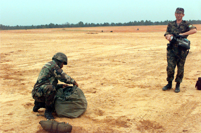 A soldier from the U.S. Army's 82nd Airborne Division stows his parachute after a jump from a U.S. Air Force C-17 at Sicily drop zone at Fort Bragg, while a videographer from Kazakstan looks on. This practice jump is in preparation for the joint exercise between the 82nd Airborne Division and troops from central Asia and other countries, including Russia and Turkey. It will combine airborne operations, weapons training, and cultural exchanges in order to strengthen the partnership between all the participants while improving conditions for a successful partnership for peace exercise