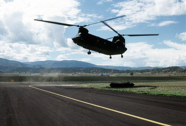 A CH-47 from Detachment 1, Company G, 140th Aviation, Nevada Army National Guard returns to Eagle County Airport with a Mark V Zodiac boat suspended by cables. The boat was used by Navy personnel to search the lakes around Gold Dust Peak for the missing bombs from the A-10 that crashed