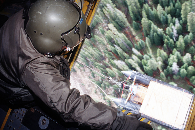 A flight engineer on the CH-47 helicopter from Detachment 1, Company G, 140th Aviation, Nevada Army National Guard keeps an eye on the Mark V Zodiac boat being airlifted that was used to search the lakes and ponds for the 500 pound Mark 82 bombs carried by the A-10 that crashed on nearby Gold Dust Peak