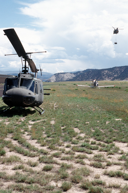 While a UH-1N helicopter sits on the ground (left), a CH-47 (upper right) from Detachment 1, Company G, 140th Aviation, Nevada Army National Guard returns with a Mark V Zodiac boat suspended by cables. The boat was used by Navy personnel to search the lakes around Gold Dust Peak for the missing bombs from the A-10 that crashed