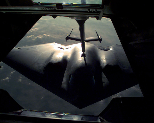 A close up view of a US Air Force B-2 Spirit Bomber from 509th Bomb Wing, Whiteman AFB, MO being refueled by the boom and refueling arm of a KC-10 Extender aircraft. The image was taken from the Boom Operators position